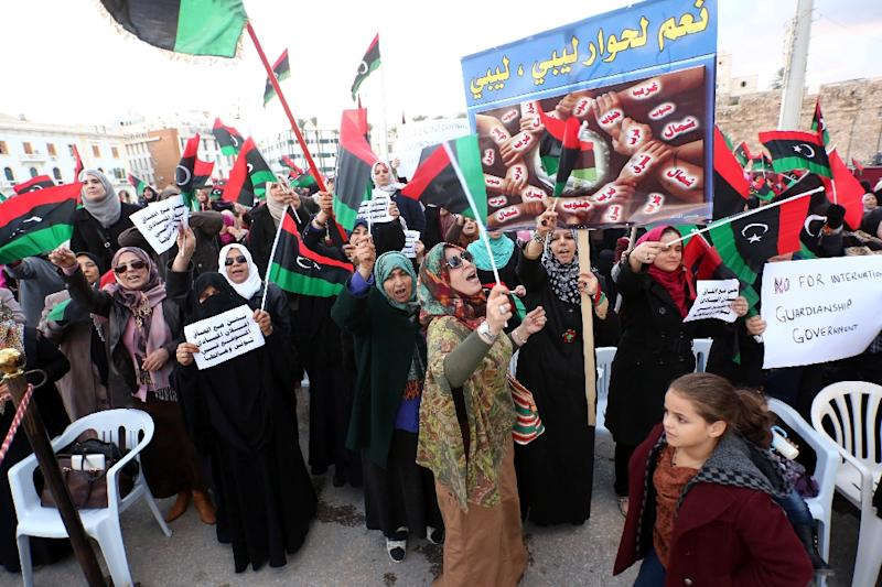 Libyan protesters wave national flags shouting slogans during a demonstration against an UN-sponsored agreement on forming a national unity government in the capital Tripoli on December 18, 2015