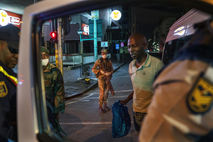 South African Defense Forces and police check a minibus driver who violated the lockdown downtown Johannesburg, South Africa, Friday, March 27, 2020. Police and army started patrolling moments after South Africa went into a nationwide lockdown for three weeks in an effort to mitigate the spread to the coronavirus. The new coronavirus causes mild or moderate symptoms for most people, but for some, especially older adults and people with existing health problems, it can cause more severe illness or death.(AP Photo/Jerome Delay)