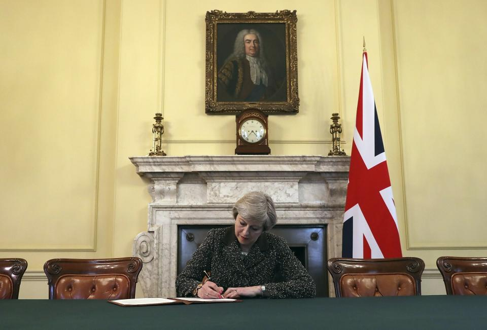 FILE - In this Tuesday March 28, 2017 file photo, Britain's Prime Minister Theresa May, sitting below a painting of Britain's first Prime Minister Robert Walpole, signs the official letter to European Council President Donald Tusk, in 10 Downing Street, London, invoking Article 50 of the bloc's key treaty, the formal start of exit negotiations. Britons voted in June to leave the bloc after four decades of membership. (Christopher Furlong/Pool Photo via AP, File)