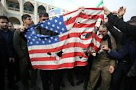 """Iranians burn a US flag during a demonstration against American """"crimes"""""""