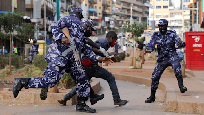 Police officers chase a man in Kampala, Uganda - Friday 25 June 2021