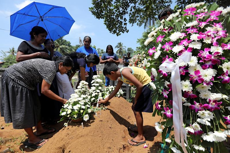 Family put flowers on the grave of Rexy Duglas, 67, at a cemetery near St Sebastian's Church in Negombo, Sri Lanka. (REUTERS)