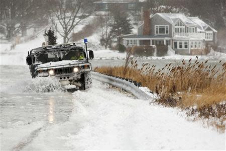 A police vehicle drives through a flooded street during a winter nor'easter snow storm in Scituate, Massachusetts January 3, 2014. REUTERS/Dominick Reuter
