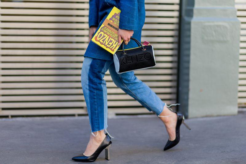 The lower half of a woman who is wearing frayed denim and black pumps.