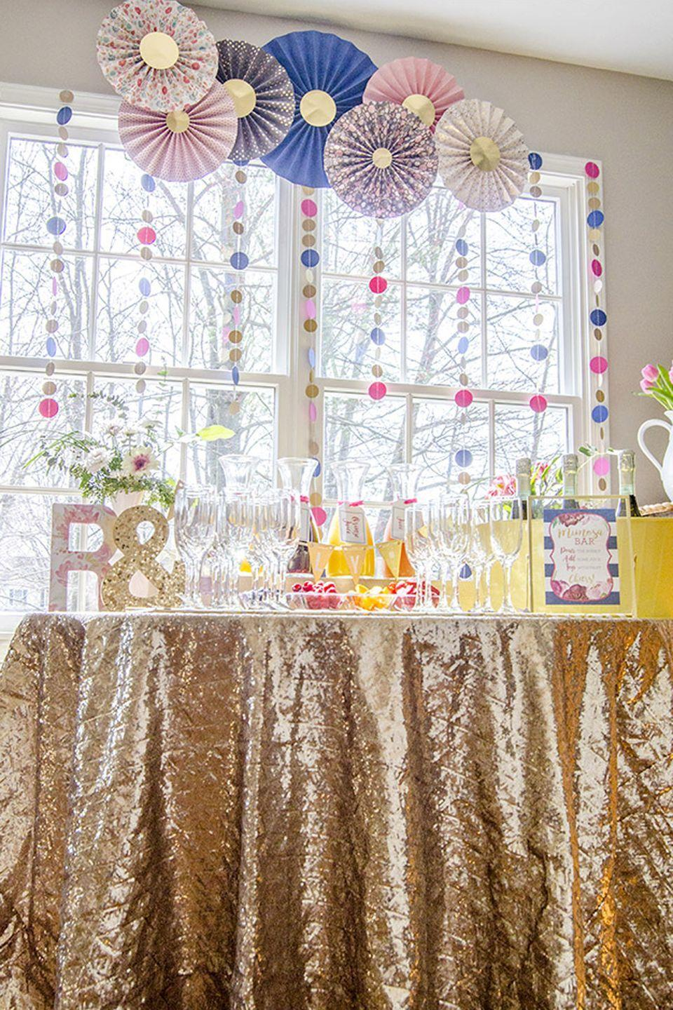 """<p> Dress up your bar with a sparkly tablecloth. A paper garland and glittery rosettes will make it a focal point of any party. </p><p>See more at <a href=""""https://www.unoriginalmom.com/how-to-create-a-bridal-shower-mimosa-bar/"""" rel=""""nofollow noopener"""" target=""""_blank"""" data-ylk=""""slk:Unoriginal Mom"""" class=""""link rapid-noclick-resp"""">Unoriginal Mom</a>.<br></p>"""