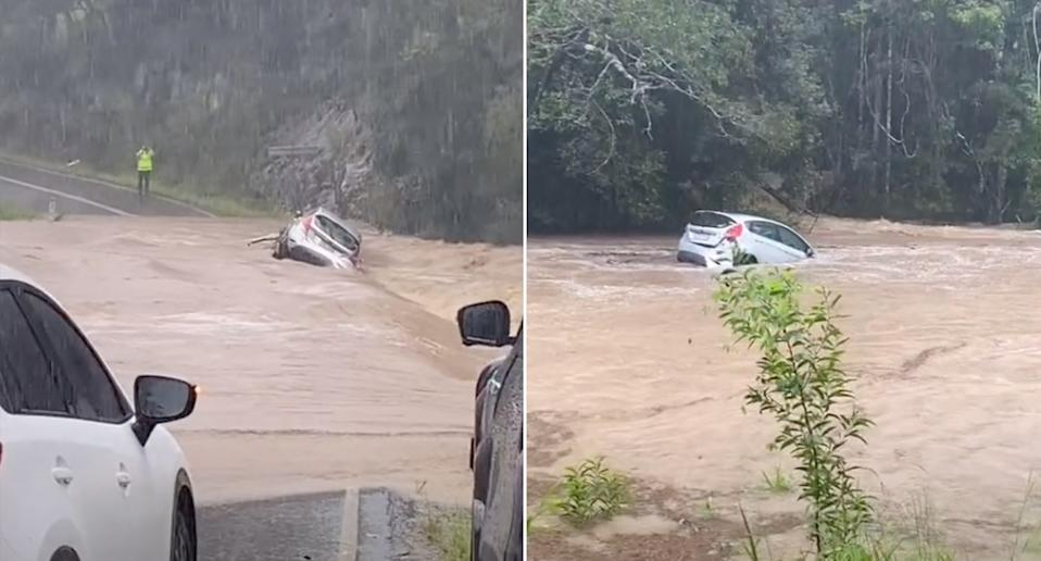 A car being swept away by floodwaters.