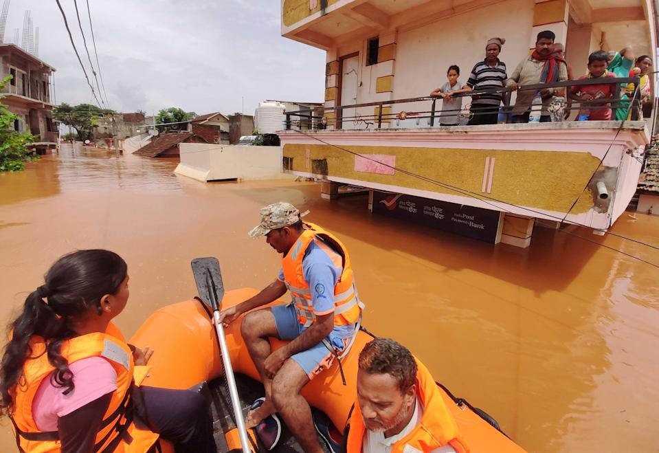 People await for help on top floor of their house after village submerged in water at Kolhapur in western Maharashtra state, India (AP)