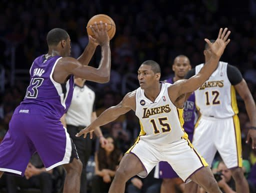 Sacramento Kings guard Tyreke Evans (13) looks to pass as Los Angeles Lakers forward Metta World Peace (15) defends in the first half of an NBA basketball game in Los Angeles Saturday, March 17, 2013. (AP Photo/Reed Saxon)