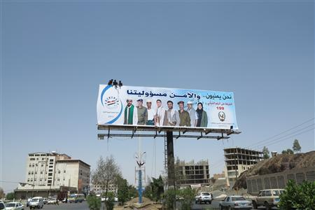 Workers put up a billboard urging citizens to cooperate with security authorities in Sanaa