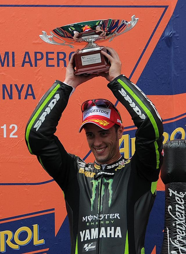 Monster Yamaha Tech 3's Italian Andrea Dovizioso celebrates on the podium after the MotoGP race of the Catalunya Moto GP Grand Prix at the Catalunya racetrack in Montmelo, near Barcelona, on June 3, 2012. Yamaha Factory Racing's Spanish Jorge Lorenzo won the race ahead of Repsol Honda Team's Spanish Dani Pedrosa and Monster Yamaha Tech 3 Italian Andrea Dovizioso. AFP PHOTO / LLUIS GENELLUIS GENE/AFP/GettyImages