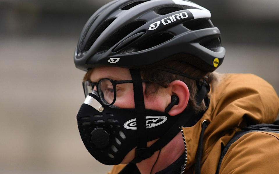 A cyclist wears a helmet and a mask as they travel by bicycle along a road in London on March 2, 2020. (Photo by DANIEL LEAL-OLIVAS / AFP) (Photo by DANIEL LEAL-OLIVAS/AFP via Getty Images) - DANIEL LEAL-OLIVAS/AFP via Getty Images