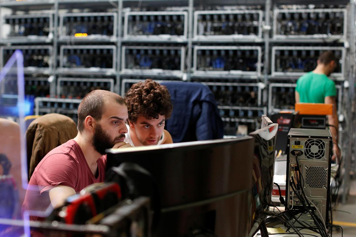 Employees work on bitcoin mining computers at Bitminer Factory in Florence, Italy