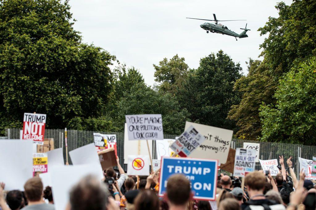 <p>Activists protest outside the London residence of US ambassador Woody Johnson as Marine One arrives at to pick up the President and First Lady.</p>