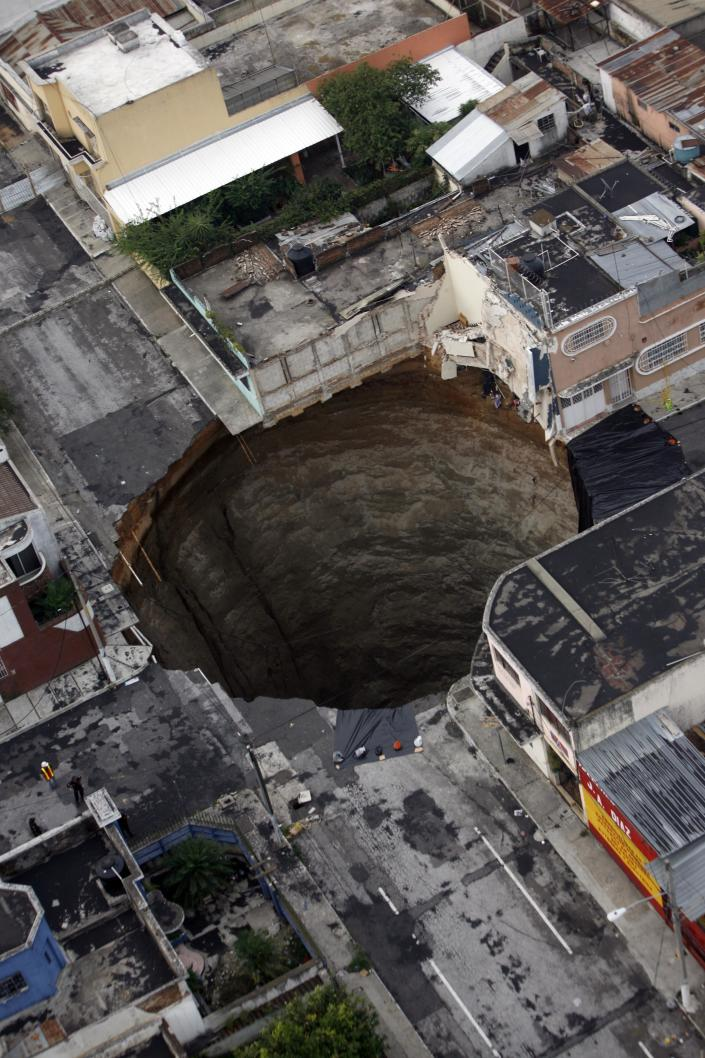 A sinkhole covers a street intersection in downtown Guatemala City, Wednesday, June 2, 2010. Authorities blamed heavy rains caused by tropical storm Agatha as the cause of the crater that swallowed a a three-story building but now say they will be conducting further studies to determine the cause. (AP Photo/Moises Castillo)