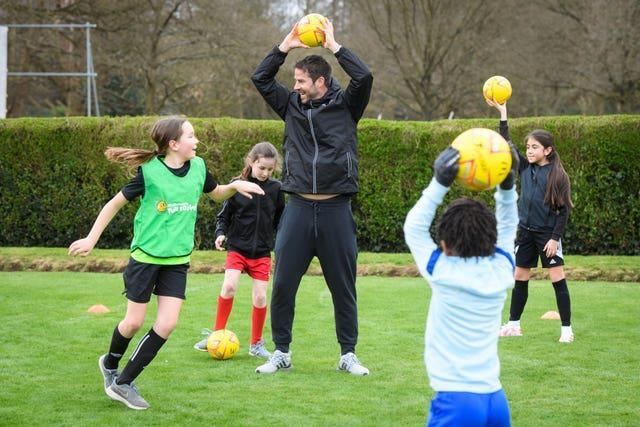 Former Liverpool and Tottenham midfielder Jamie Redknapp holds a ball above his head in a coaching session with young children