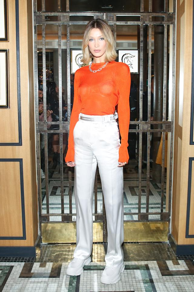 The supermodel, who's also a face of Dior, took a break from walking the runway to attend the dinner in a pair of silky white pants, a tangerine top, and sneakers, which she paired with a simple gold chain necklace and a tousled bob.