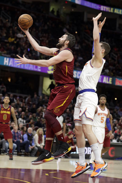 Cleveland Cavaliers' Kevin Love, left, drives to the basket against New York Knicks' Mario Hezonja, from Croatia, in the first half of an NBA basketball game, Monday, Feb. 11, 2019, in Cleveland. (AP Photo/Tony Dejak)