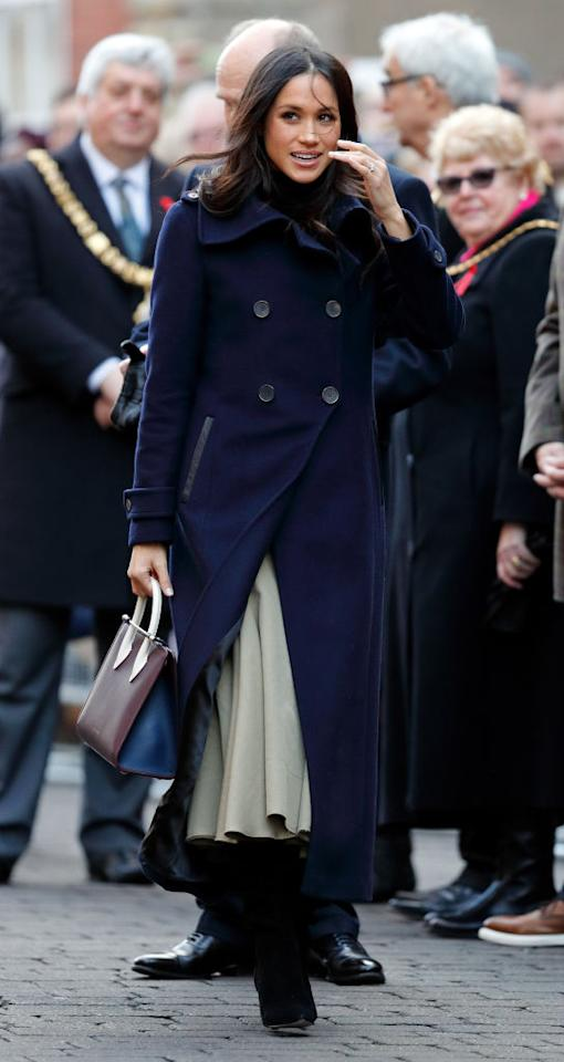 <p>On her first royal outing hand-in-hand with Prince Harry, the former actress flew the sartorial flag for Canada in a double-breasted navy coat by Mackage. But most notably, she eschewed royal tradition in favour of a handbag by Scottish brand, Strathberry.<br />It is regarded against royal protocol for female members of the Royal Family to carry large handbags. For instance, the Duchess of Cambridge will often use a clutch in order to avoid the awkward etiquette of hand-shaking while carrying out public engagements. And her rule-breaking accessory hints at a shift in royal codes of conduct. <em>[Photo: Getty]</em> </p>