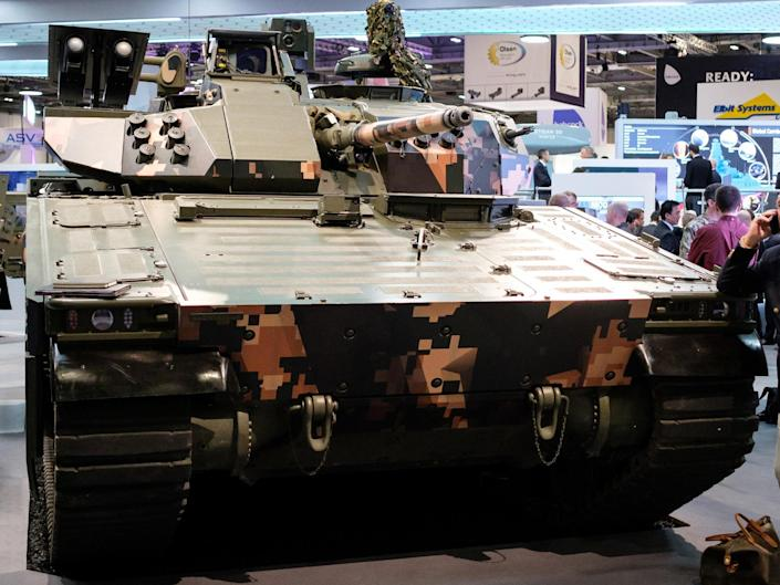 A man chats on his phone as he leans on a CV90 Battle Station in the 'BAE Systems' display area at the DSEI event at the ExCel centre: Getty