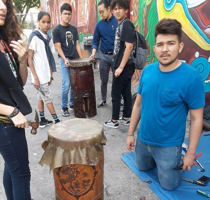 Antonio Tlaloc Carrillo, right, re-skinning a drum with other students at Semillas Community Schools in 2017.