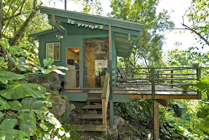 """<p>Set in a lush tropical paradise, the 250-square-foot Sunset Beach Treehouse Bungalow in Haleiwa, Hawaii overlooks one of the North Shore's most famous surf spots. Renters climb a 100-step stone path to reach the structure, nestled among black lava rocks and a leafy canopy of Banyan, avocado, and mango trees. Featuring a full-size bed as well as a lofted sleeping area, the treehouse sleeps as many as three people, and includes a kitchenette and bathroom. Rental rates start from $1,200 per week. </p><p><a class=""""link rapid-noclick-resp"""" href=""""https://www.airbnb.com/rooms/38944"""" rel=""""nofollow noopener"""" target=""""_blank"""" data-ylk=""""slk:PLAN YOUR TRIP"""">PLAN YOUR TRIP</a></p>"""