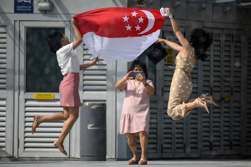 TOPSHOT - Women holding the Singapore national flag pose for a photograph at the Merlion Park to mark the 55th National Day celebrations in Singapore on August 9, 2020. (Photo by Roslan RAHMAN / AFP) (Photo by ROSLAN RAHMAN/AFP via Getty Images)