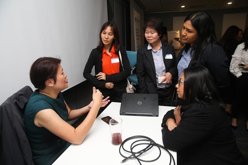 Career Comeback Programme participants getting advice from Baker Hughes APAC senior talent acquisition manager Karen Choe (left) during a workshop on October 29. — Picture by Choo Choy May
