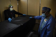 FILE - In this Jan. 9, 2021, file photo, transporters Miguel Lopez, right, Noe Meza move a body of a COVID-19 patient to a morgue at Providence Holy Cross Medical Center in the Mission Hills section of Los Angeles. The U.S. death toll from COVID-19 has topped 500,000 — a number so staggering that a top health researchers says it is hard to imagine an American who hasn't lost a relative or doesn't know someone who died. (AP Photo/Jae C. Hong, File)