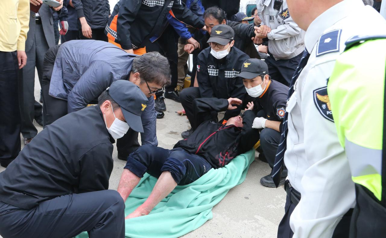 """ATTENTION EDITORS - VISUAL COVERAGE OF SCENES OF INJURY OR DEATH An injured passenger rescued by South Korean maritime policemen from a sinking ship in the sea off Jindo, is treated at a port in Jindo April 16, 2014. About 160 passengers, including high school students, were plucked to safety on Wednesday in a dramatic rescue from a South Korean passenger ferry """"Sewol"""" sinking with 475 on board, officials said, although at least two people had died. REUTERS/Park Cheol-hong/Yonhap (SOUTH KOREA - Tags: DISASTER MARITIME) ATTENTION EDITORS - THIS IMAGE WAS PROVIDED BY A THIRD PARTY. FOR EDITORIAL USE ONLY. NOT FOR SALE FOR MARKETING OR ADVERTISING CAMPAIGNS. THIS PICTURE IS DISTRIBUTED EXACTLY AS RECEIVED BY REUTERS, AS A SERVICE TO CLIENTS. NO SALES. NO ARCHIVES. SOUTH KOREA OUT. NO COMMERCIAL OR EDITORIAL SALES IN SOUTH KOREA"""