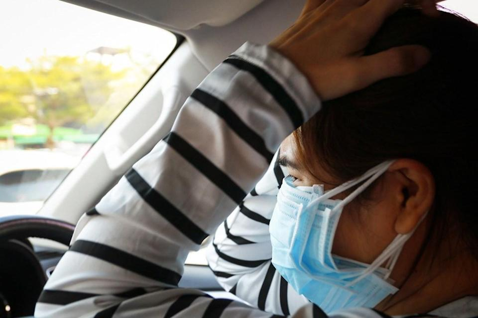 woman wearing too many masks scared
