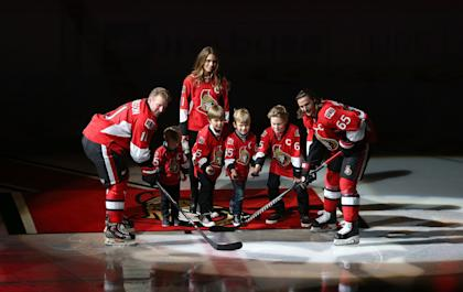 Alfredsson, with his wife and four sons, takes the ceremonial faceoff with protege Erik Karlsson. (Getty)