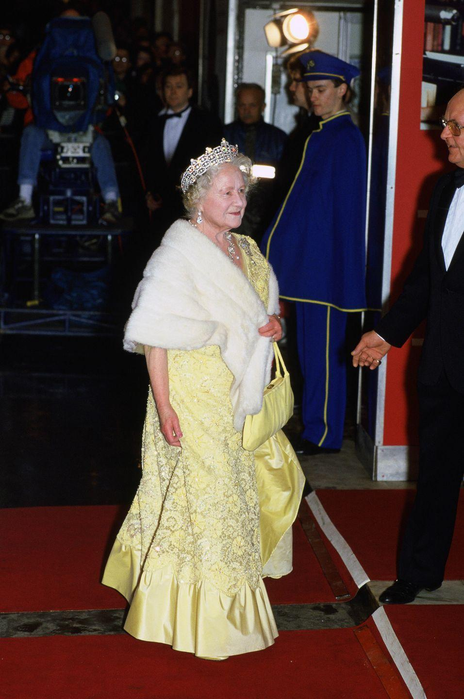 <p>Under the Queen Mother's white fur stole is a beaded Belle-yellow dress, which she wore to the premiere of <em>84 Charing Cross Road </em>in 1987. </p>