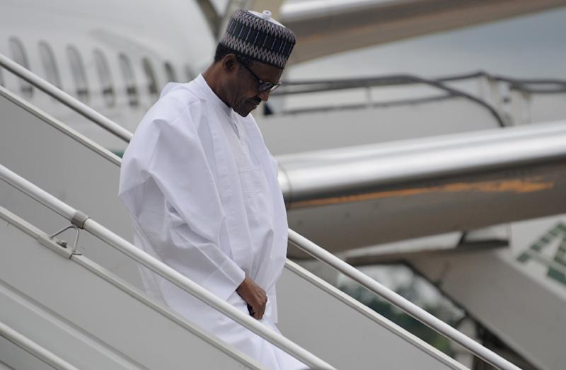 President of Nigeria Muhammadu Buhari walks down the steps of his aircraft following his arrival at the airport in Yaounde on July 29, 2015