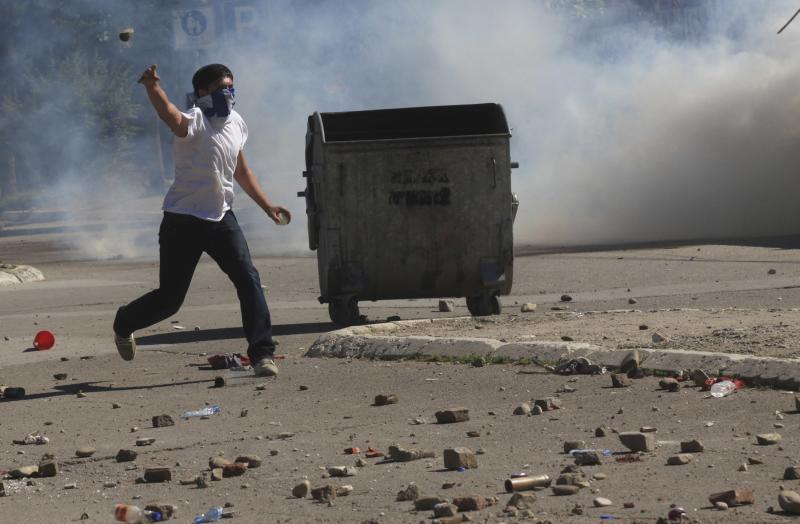 A Kosovo Albanian throws a rock towards police during a protest in the ethnically divided town of Mitrovica