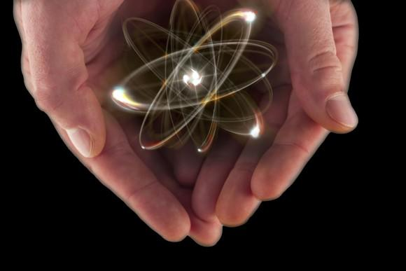 A visualization of an atom in a pair of cupped hands.