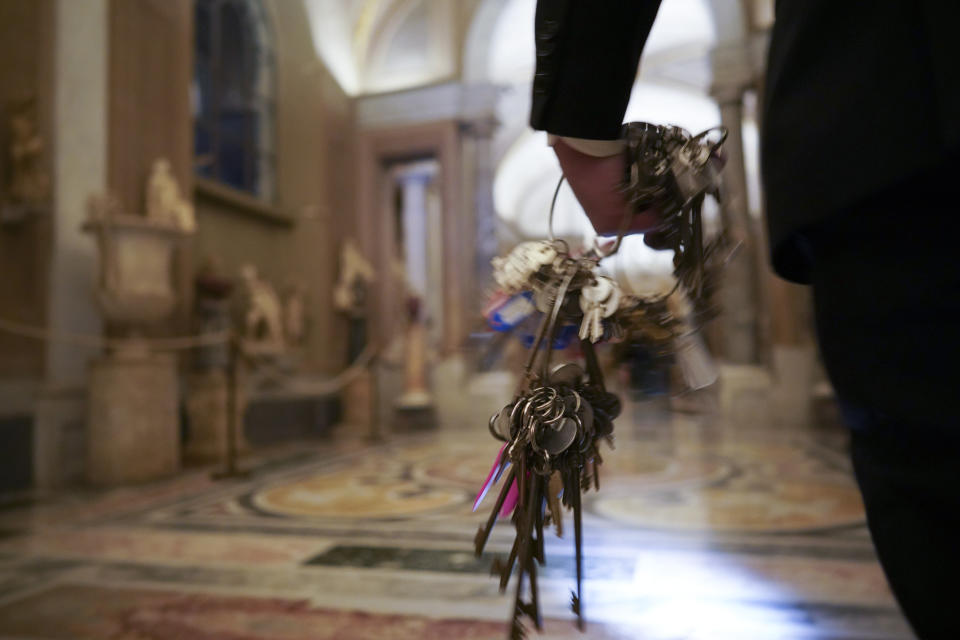 "Gianni Crea, the Vatican Museums chief ""Clavigero"" key-keeper, holds a bunch of keys as he walks to open the museum's rooms and sections, at the Vatican, Monday, Feb. 1, 2021. Crea is the ""clavigero"" of the Vatican Museums, the chief key-keeper whose job begins each morning at 5 a.m., opening the doors and turning on the lights through 7 kilometers of one of the world's greatest collections of art and antiquities. The Associated Press followed Crea on his rounds the first day the museum reopened to the public, joining him in the underground ""bunker"" where the 2,797 keys to the Vatican treasures are kept in wall safes overnight. (AP Photo/Andrew Medichini)"