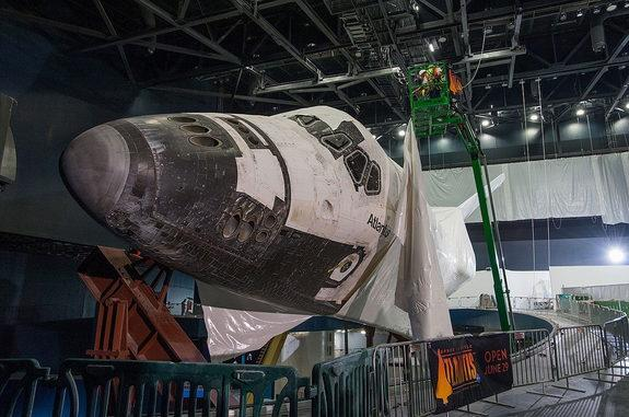 Construction workers at the Kennedy Space Center Visitor Complex in Florida carefully remove a section of plastic shrink wrap from the space shuttle Atlantis inside the $100 million exhibit dedicated to the retired NASA orbiter, April 25, 2013.