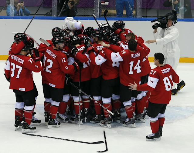 Canada forward Sidney Crosby goes to join his teammates as they celebrate after the men's gold medal ice hockey game against Sweden at the 2014 Winter Olympics, Sunday, Feb. 23, 2014, in Sochi, Russia. Canada won 3-0 to win the gold medal. (AP Photo/David J. Phillip )
