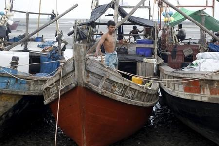 A Muslim Rohingya man stands on a boat at a fishing port at a refugee camp outside Sittwe