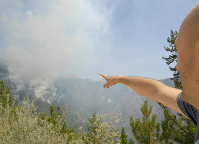 A Bosnian points at the raging wildfires, near the Bosnian town of Konjic, 40 kms south of Sarajevo, Bosnia on Thursday, Aug. 9, 2012. As firefighters tried to contain two wildfires near an ammunition factory in southern Bosnia on Thursday, one of the blazes began setting off explosions in a minefield left over from the country's war in the 1990s, officials said. (AP Photo/Sulejman Omerbasic)