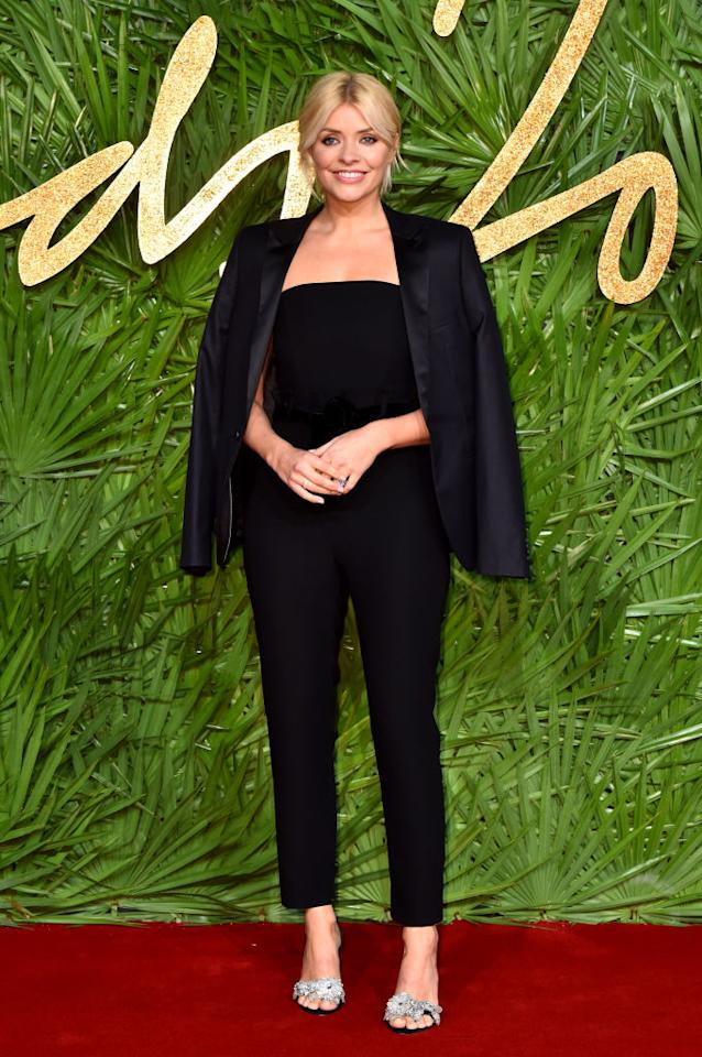<p>Holly Willoughby just gave fashion fans another look to coo over this season as she donned a black jumpsuit by House of Fraser on the red carpet. She finished the look with a blazer draped over her shoulders (it's the fashion way). [<em>Photo: Getty]</em> </p>