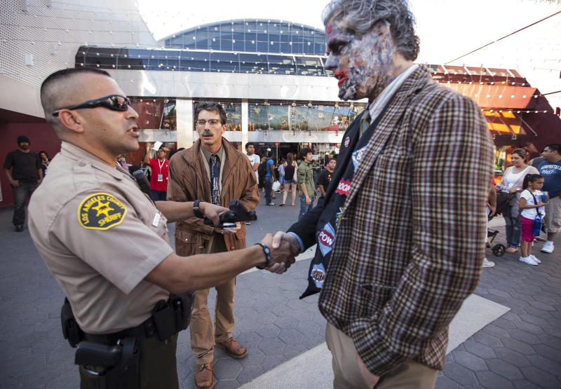 """This July 19, 2012 photo shows Los Angeles County Sheriff Calvillo, left, withholding toy guns from Batman fans from Indiana, Brian Haughs, 28, right, dressed as the character Two-Face, and John Werskey, dressed as Commissioner James Gordon, while waiting for the midnight premiere of """"The Dark Knight Rises,"""" at Universal CityWalk in Los Angeles. A gunman wearing a gas mask set off an unknown gas and fired into the crowded movie theater in Aurora, Colo., Friday July 20, 2012, killing 12 people and injuring at least 50 others, authorities said. (AP Photo/Damian Dovarganes)"""