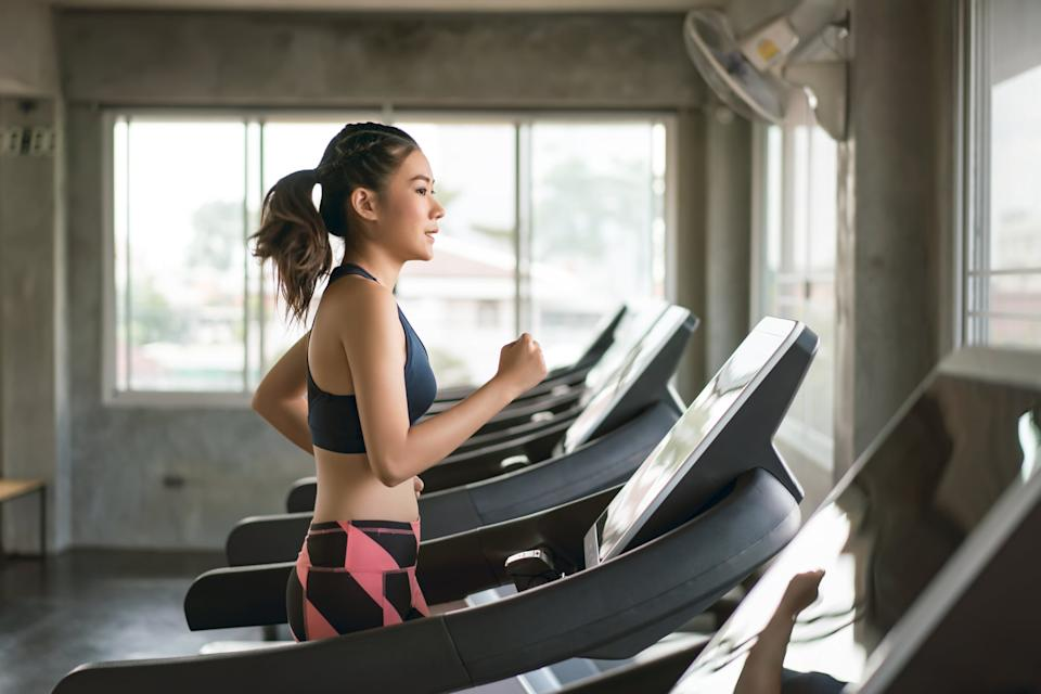 Young women in sportswear running on treadmill at gym
