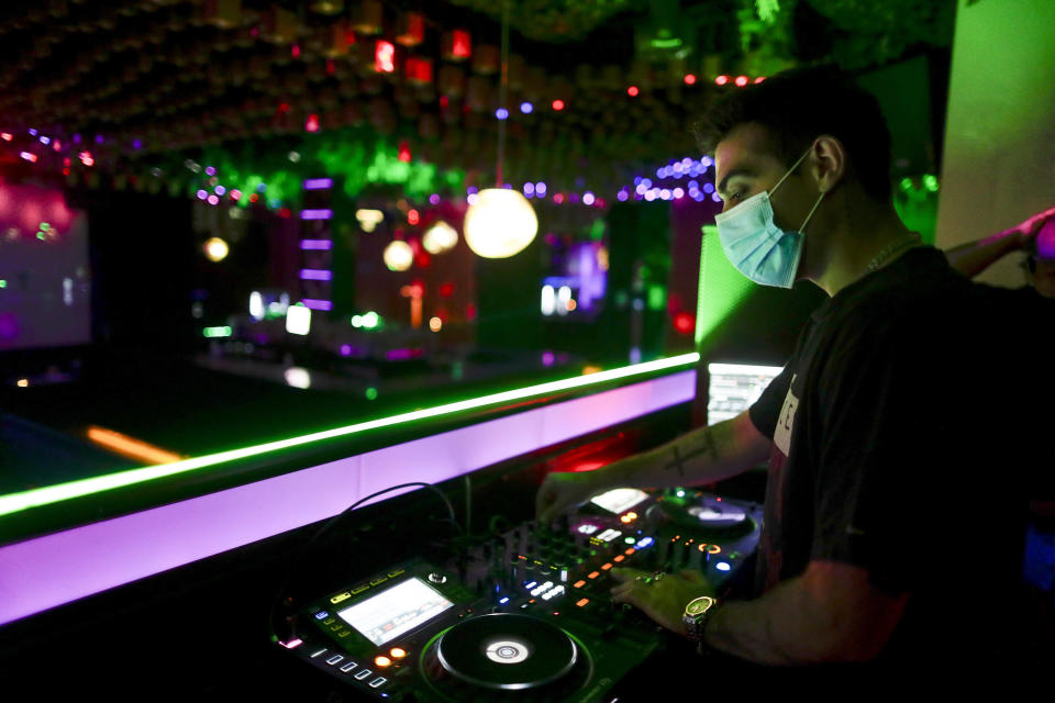 A DJ performs in a discotheque in Madrid, Spain, early Saturday, July 25, 2020. Nightlife is becoming the new target of Spanish authorities attempting to contain a spike in coronavirus infections since the country ended a lockdown. The Catalonia regional government has shut nightlife venues in Barcelona, and on Friday officials in Madrid said they were considering a similar step. (AP Photo/Manu Fernandez)