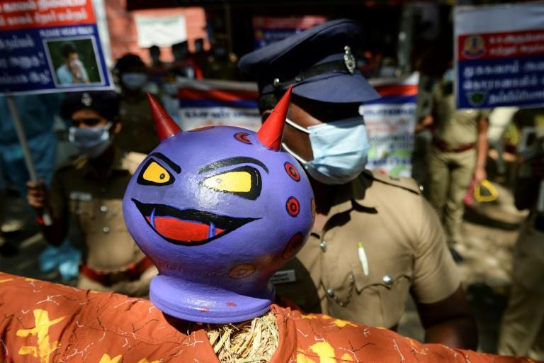 A policeman holds an effigy of a demon representing the coronavirus during an awareness campaign in Chennai, India