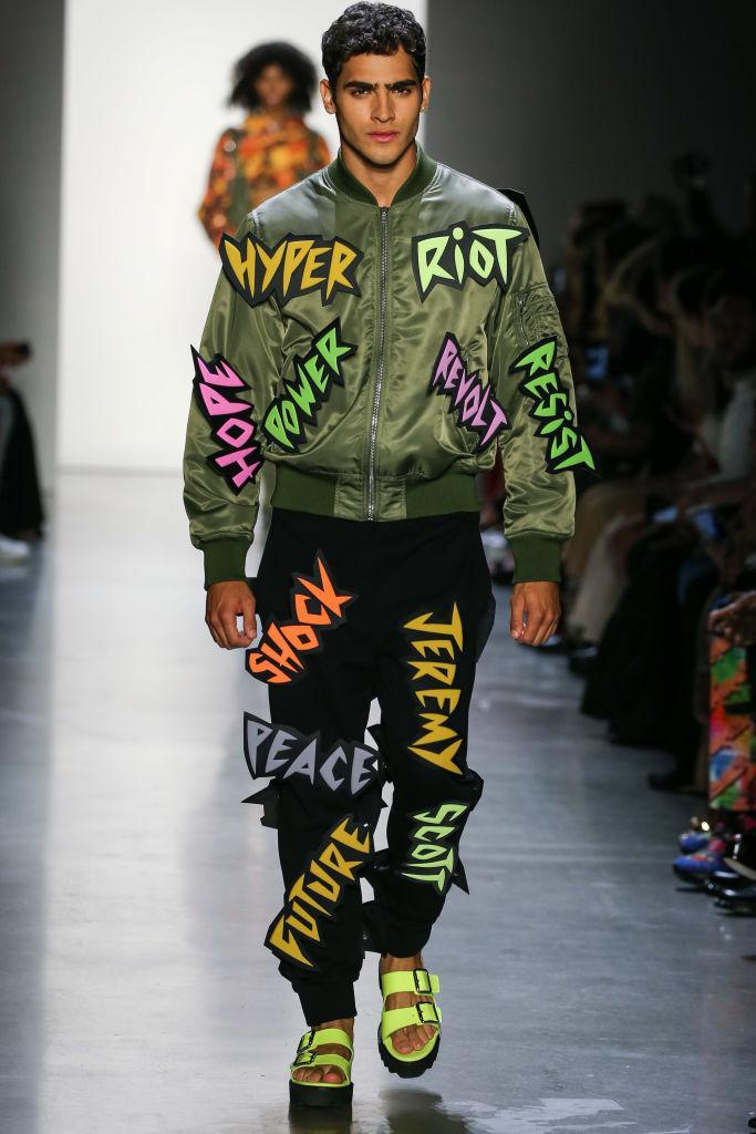 """<p>The political messaging saying to """"resist"""" and """"revolt"""" is also translated to Scott's menswear; a model is seen here wearing an army-green bomber jacket and black trousers with similar language plastered throughout his clothing. (Photo: Getty) </p>"""
