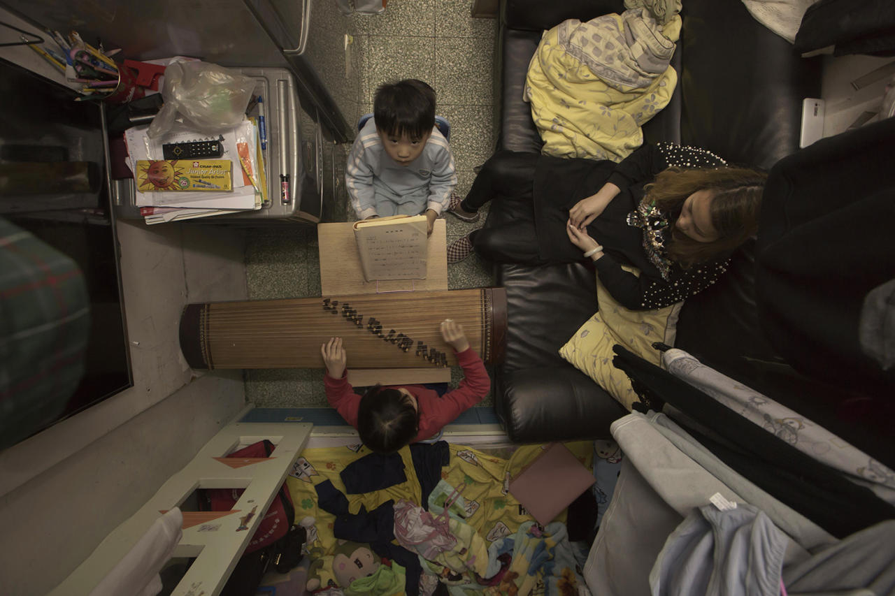 <p>Li Suet-wen and her son, 6, and daughter, 8, live in a 120-square-foot room crammed with a bunk bed, small couch, refrigerator, washing machine and small table, in an aging walkup in Hong Kong that she pays $580 per month for in rent and utilities. That's nearly half the $1,290 she earns monthly at a bakery decorating cakes. (Photo: Kin Cheung/AP) </p>