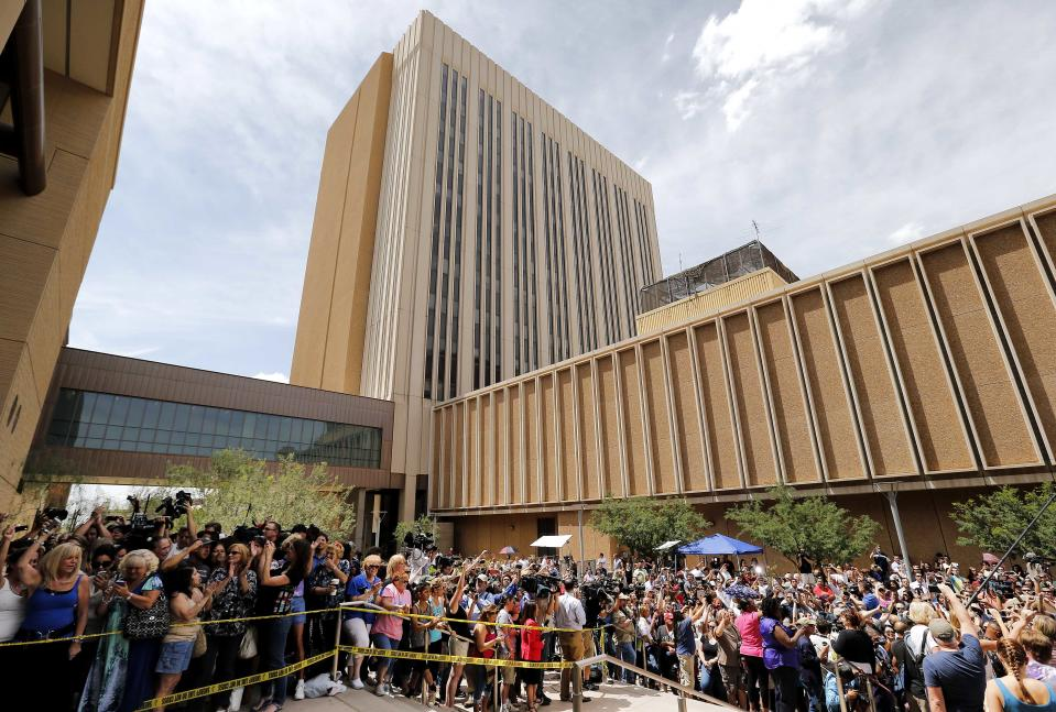 Spectators wait outside Superior Court in Phoenix, Wednesday, May 8, 2013 for a verdict in the trial of Jodi Arias, a waitress and aspiring photographer charged with killing her boyfriend, Travis Alexander, in Arizona in 2008. The four month trial included graphic details of their sexual escapades and photos of Alexander just after his death. (AP Photo/Matt York)