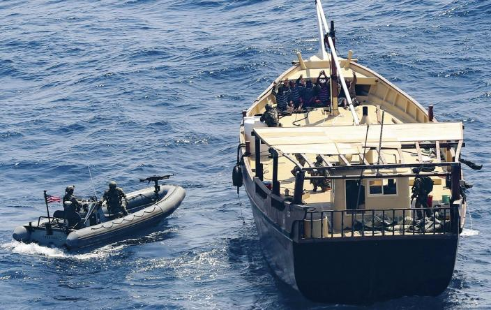 In this Friday, Feb. 12, 2021 photo released by the U.S. Navy, the guided-missile destroyer USS Winston S. Churchill boarded a stateless dhow off the coast of Somalia and interdicted an illicit shipment of weapons and weapon components. The U.S. Navy said on Tuesday, Feb. 16, that it seized a large cache of weapons, including Kalashnikov-style rifles and rocket-propelled grenade launchers, being smuggled by ships off the coast of Somalia. (Mass Communication Specialist 3rd Class Louis Thompson Staats IV/U.S. Navy via AP)