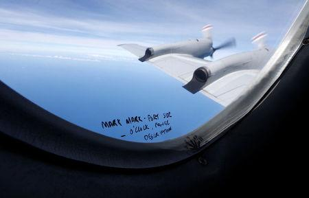 FILE PHOTO - Hand-written notes on how a crew member should report the sighting of debris in the southern Indian Ocean is pictured on a window aboard a Royal New Zealand Air Force P-3K2 Orion aircraft searching for missing Malaysian Airlines flight MH370, March 22, 2014.  REUTERS/Jason Reed/File Photo